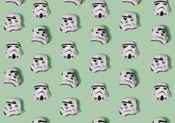 Pattern created of white Stormtrooper helmets from three positions – front, left and right sides. A top view with pastel green background.
