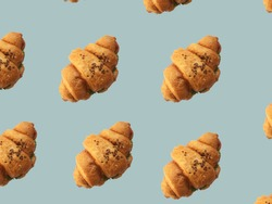 Pattern from croissants isolated on gray background. Bakery pattern with baked croissant. Fresh croissant with salad and grains pattern. Croissant cookies sprinkled with grains on a brown background
