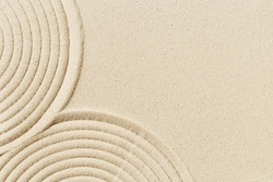 Pattern in Japanese Zen Garden with close up concentric circles on sand for meditation and tranquility. Aesthetic minimal sandy background. Selective focus.