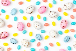 Pattern  made of Easter candy chocolate eggs and Jellybean on white background