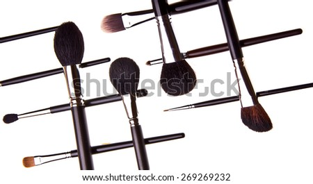 Pattern made of essential professional make-up brushes on white background. Overhead view. Black and white kit.