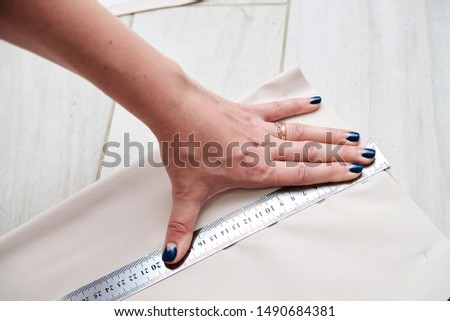 Pattern making process, Hand with blue manicure, holding ruler on light beige fabric. Close-up picture of sewing tutorial. Young woman fashion designer, showing how to make pattern. Handmade workshop.