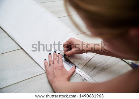 Pattern making process, Hands, holding ruler and drawing with chalk on paper fabric. Close-up picture of sewing tutorial. Young woman fashion designer, showing how to make pattern, Handmade workshop.