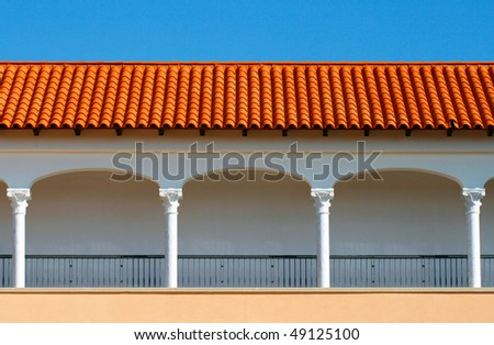 Pattern of a modern covered gallery with the tile roof on blue sky background.It is stylized to classical Spanish style. Caesarea, Israel.