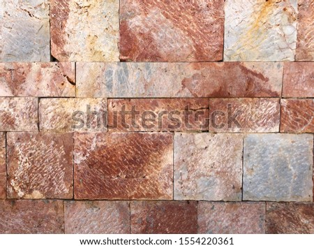 Pattern of decorative red stone wall background.Stone wall texture. random size stone wall.Background of stone wall. #1554220361