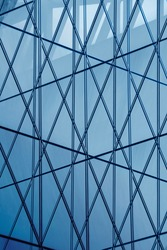 Pattern of glass wall reflecting sky. Abstract modern architecture background. Close-up fragment of an office building exterior. Geometric structure with triangular and polygonal ornament of panels.