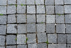 Pattern of grey cement tiles on the floor. Uneven and broken pavement. close up street background