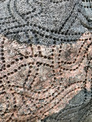 Pattern of holes in rock that looks like tracks or trails, good for abstractly symbolizing networks and connections or movement and transportation, organizational structure webs, modern art