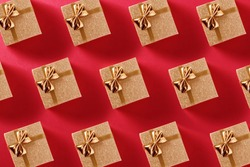 Pattern of many small golden gifts on a red background for Christmas, birthdays, anniversaries, Valentine's Day. View from above.
