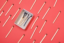 pattern of matches and a box of burnt matches on a red background