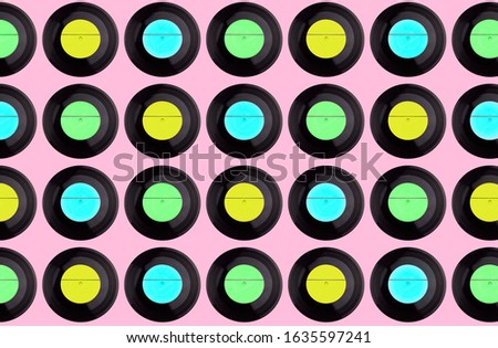 pattern of multicolored vinyl discs on a pink background