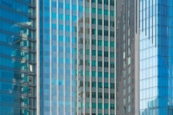Pattern of office buildings windows. Glass architecture facade design with reflection in urban city, Downtown Dubai. Urban city in financial district with blue sky.