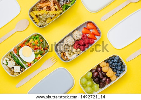 Pattern of plastic lunch boxes filled with healthy food, fresh fruits and berries with wooden forks and spoons on yellow background. Top view, flat lay.