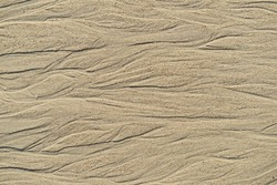 Pattern of sand erosion make beautiful line and curve on the beach