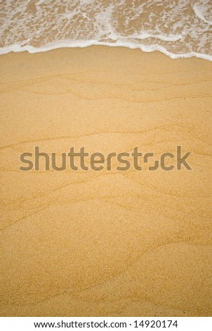Pattern of sandy beach with waves approaching.