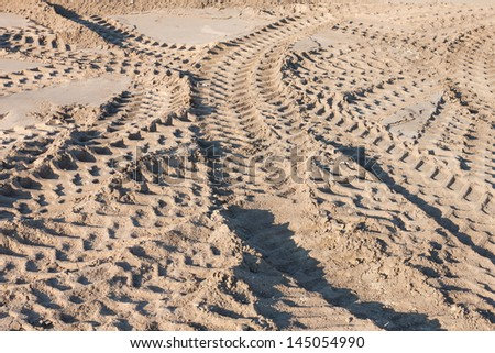 pattern of tractor wheel printed on sand road use as nature background