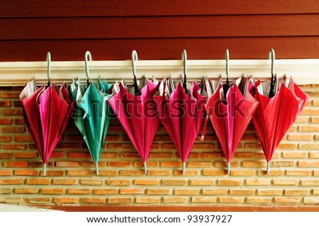 Pattern of umbrella hang on cement and wood wall