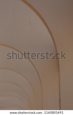 Pattern of white painted concrete arches. Top of an exterior building corridor with repetitive rounding shapes. Modern design with curved lines and black shadows. Abstract architectural image.   #1160805691