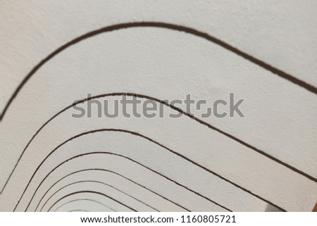 Pattern of white painted concrete arches. Top of an exterior building corridor with repetitive rounding shapes. Modern design with curved lines and black shadows. Abstract architectural image.   #1160805721
