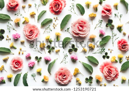 Pattern with colorful flowers and green leaves on white background. Full frame. View from above. Flat lay.