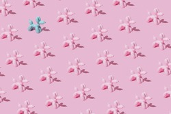 Pattern with pink ballon dogs on pastel pink backgroung with one intruder. Minimal flat lay concept.