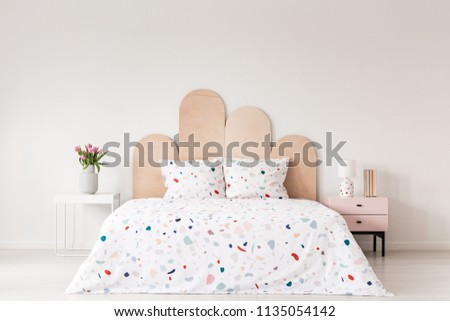 Patterned bed with headboard between table with flowers and pink cabinet in bedroom interior. Real photo #1135054142
