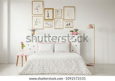 Patterned bedding on bed with bedhead in woman's bedroom interior with pink flower on table #1092572531