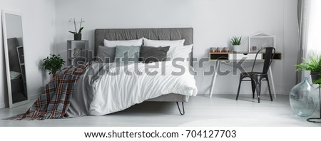 Patterned blanket in grey bedroom with black designed chair near to white desk with plant #704127703