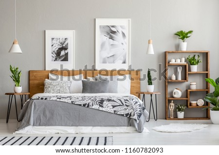 Patterned blanket on wooden bed between tables with plants in bedroom interior with posters. Real photo #1160782093