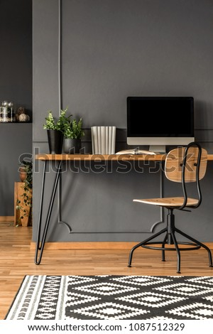 Patterned carpet in grey scandi workspace interior with computer monitor on wooden desk #1087512329