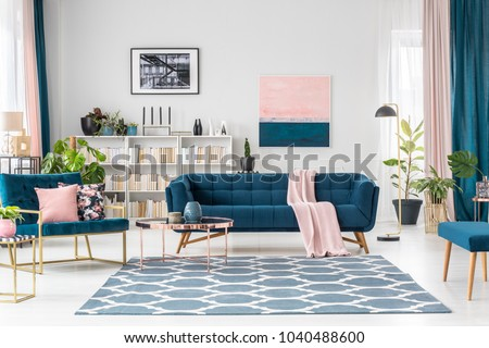 Patterned carpet in pink and blue living room interior with sofa against white wall with painting