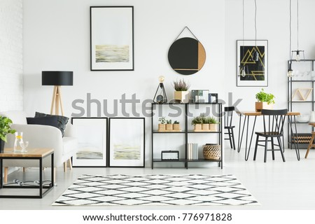 Shutterstock Patterned carpet on the floor and mirror and paintings on the wall in bright living room with sofa between table and lamp