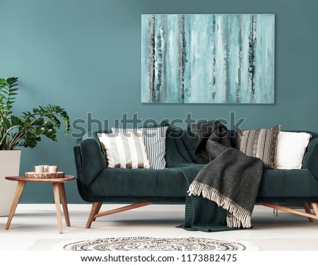 Patterned cushions on sofa next to wooden table and plant in dark apartment interior. Real photo #1173882475