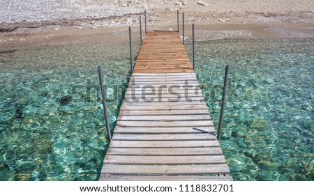 Patterned dock over the water. Wooden post supporting the walk bridge.Crystal clear water glittering under the sun. Scenic view of a travel destination.