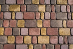 Patterned, partly wet after rain, multicoloured outdoor tile with vaious shapes