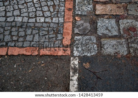 Patterned pavement background with wet dirt and fall leaves. Paved natural granite cobblestone sidewalk in park of Berlin Germany. Wet leaf and twigs on walking path dirty after rain. Retro backdrop. #1428413459