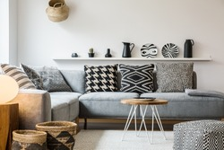 Patterned pillows on grey couch in modern living room interior with pouf and wooden table. Real photo