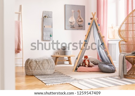 Patterned pouf on carpet next to tent with cushions in white kid's room interior with poster. Real photo