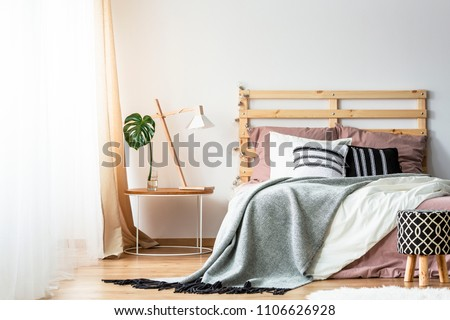 Patterned stool next to bed with wooden headboard in bedroom interior with lamp on table. Real photo #1106626928