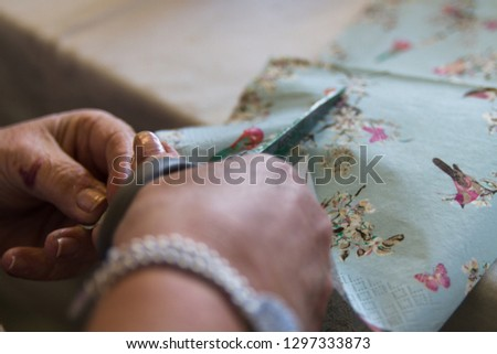 Patterned tissue paper being cut with scissors ready for use in a crafting project.  Crafting, home decor, childrens projects concepts. #1297333873