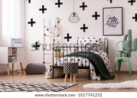 Patterned wallpaper, stool and carpet in kid's bedroom interior with cactus pillow on green chair next to bed