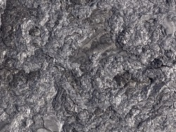 Patterns cracks and shapes from close up portion of black solidified lava, Hawaii