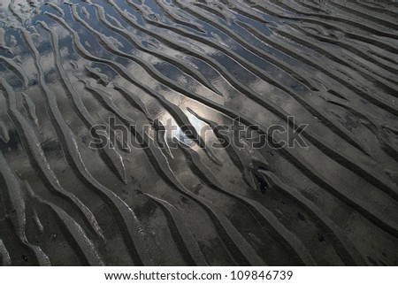 Patterns in beach sand left by water with a reflection of the sun.