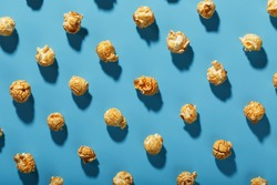 Patterns of caramel popcorn on a blue background in the form of a pattern. Full screen as a conceptual background. Hard light with shadow