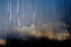 patterns on glass, frosty drawings in winter on a window, blue background and ice drawings, droplets of fody, reflection through glass,