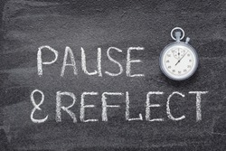 pause and reflect phrase written on chalkboard with vintage precise stopwatch