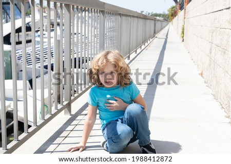 Paused for breath. Boy relax hunkering down on promenade. Boy child take short rest Stockfoto ©