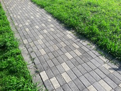 Paved lined footpath and green grass