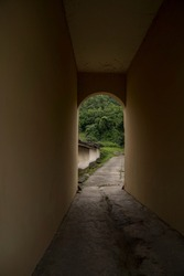 Paved path leading through a short tunnel in a medieval castle and continuing forward into a lush forested area