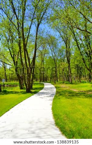 Paved Pedestrian Trail Follows Along a Winding Stream Through Woods in a Park  - Shutterstock ID 138839135